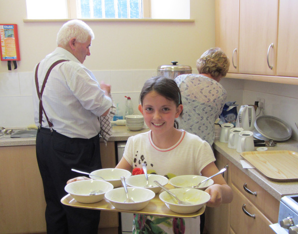 Girl carrying tray of washing up with older people in background