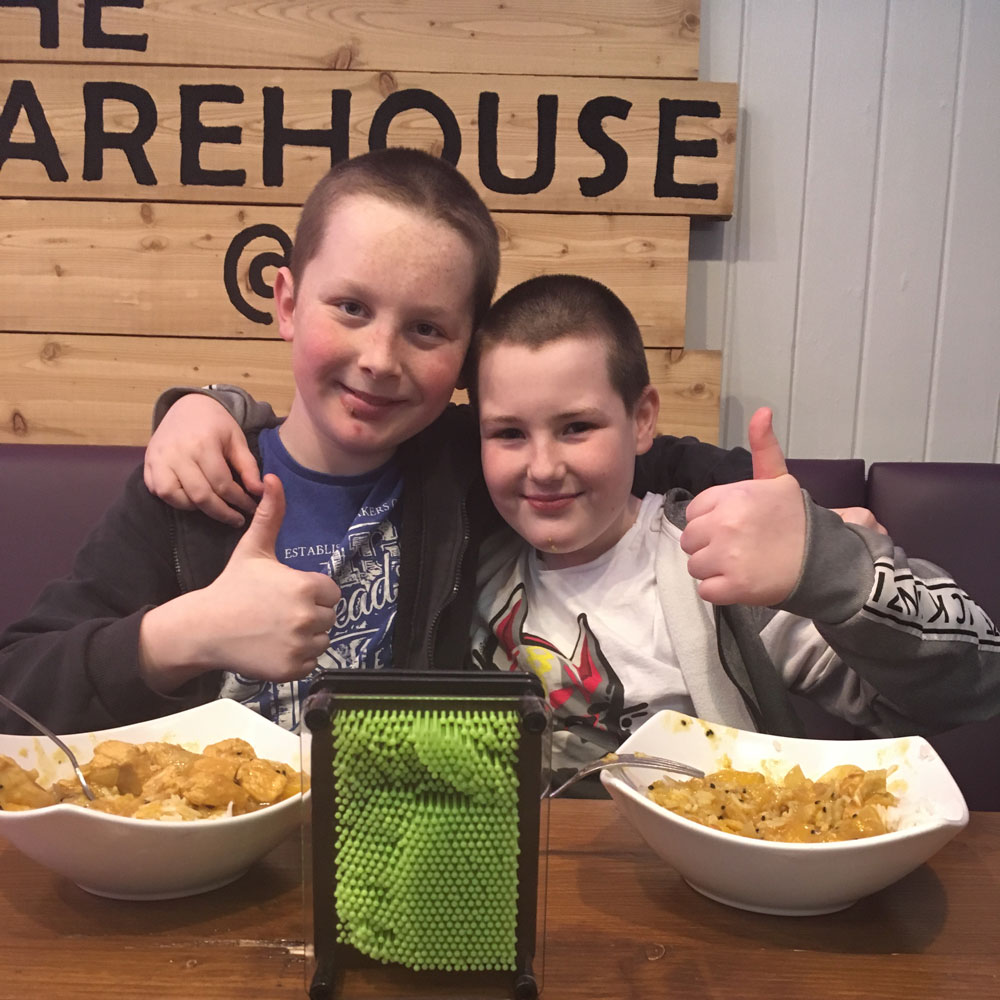 Two lads with thumbs up and bowls of food