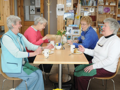 Four older women sitting around café table, laughing