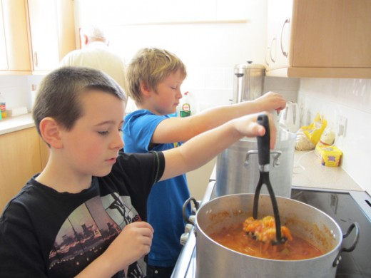 Two boys cooking a stew