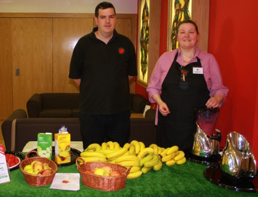 Man and woman behind table displaying bananas and other food