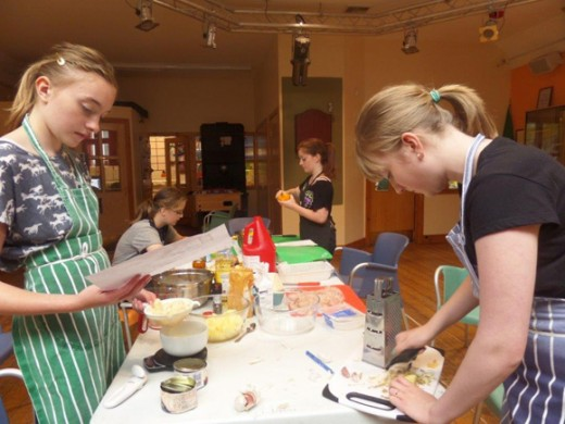 Girls preparing ingredients around a long table