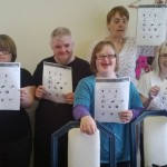 Five adults with learning disabilities holding up info sheet
