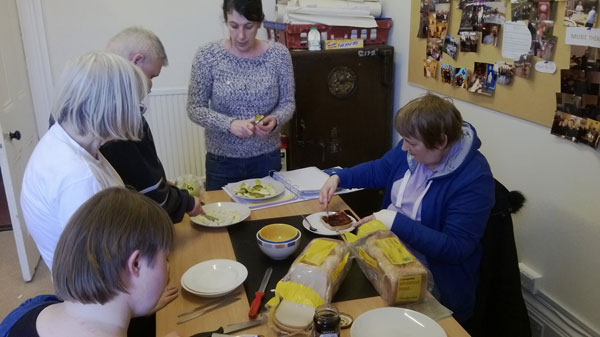 Group of four people with learning disabilities and trainer working with sliced bread and fruit