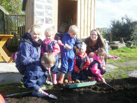 Young children digging with trowels with two young mums
