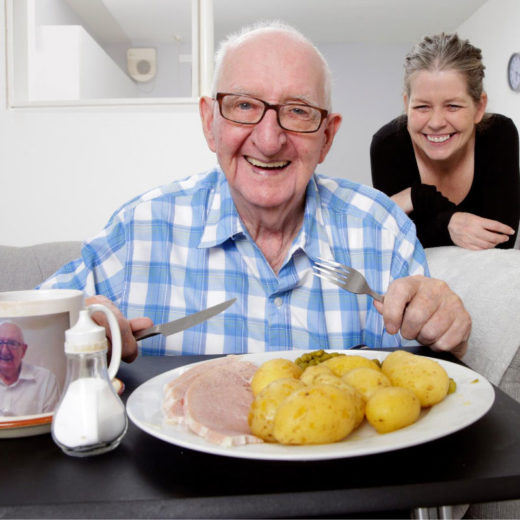 Older man eating lunch with young woman behind