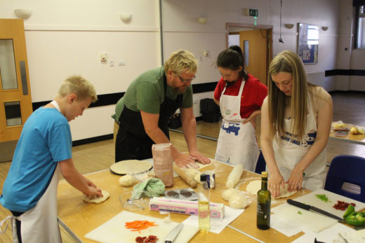Young people being taught to make pizza