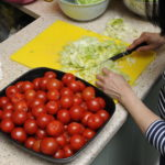 Woman chopping lettuce and tomatos