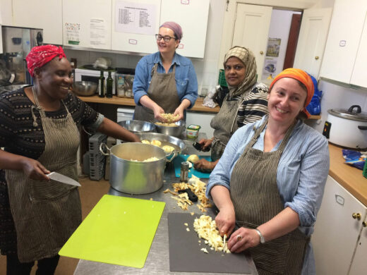 Four women cooking in community kitchen